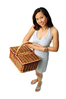Woman carrying picnic basket, looking at camera - Asia Images Group