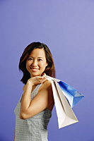 Woman carrying shopping bags over shoulder, looking at camera - Asia Images Group