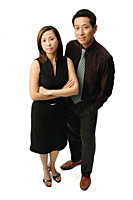 Couple standing, looking at camera, woman with arms crossed - Asia Images Group
