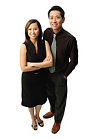 Couple standing, smiling at camera, woman with arms crossed - Asia Images Group