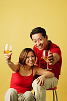 Couple sitting, raising drinks towards camera - Asia Images Group