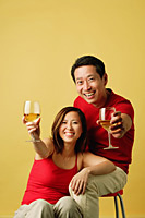 Couple holding drinks up for a toast - Asia Images Group