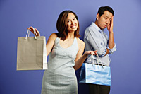 Smiling woman holding shopping bags, man behind her with hand on head - Asia Images Group