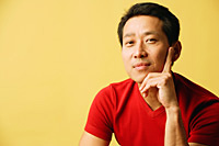 Man looking at camera, hand on chin - Asia Images Group