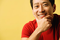 Man smiling at camera, hand on chin - Asia Images Group