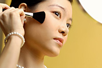 Woman putting on blusher - Asia Images Group