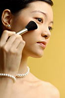 Woman putting on blusher with make up brush - Asia Images Group