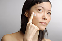 Woman applying moisturizer to face - Asia Images Group