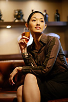 Woman with champagne glass, legs crossed, looking away - Asia Images Group