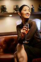 Woman with champagne glass, smiling, looking away - Asia Images Group