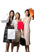 Three young women carrying shopping bags - Asia Images Group