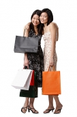 Two young women carrying shopping bags, embracing, looking at camera - Asia Images Group