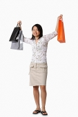 Young woman carrying shopping bags, portrait - Asia Images Group