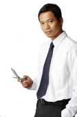 Young executive, holding mobile phone, looking at camera - Asia Images Group