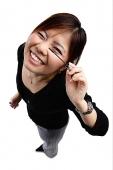 Woman applying mascara, smiling at camera - Asia Images Group