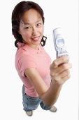 Woman holding mobile phone up, looking at camera - Asia Images Group