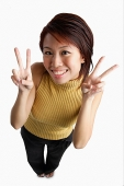 Young woman looking up at camera, making hand sign - Asia Images Group