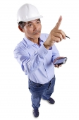 Mature man wearing construction hat, holding PDA, pointing - Asia Images Group