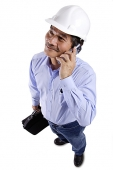 Mature man wearing construction hat, using mobile phone, looking away - Asia Images Group