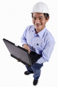 Mature man wearing construction hat, holding laptop, portrait - Asia Images Group