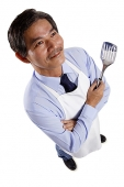 Mature man wearing apron, holding spatula - Asia Images Group