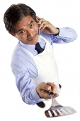 Mature man wearing apron, using mobile phone, holding spatula towards camera - Asia Images Group