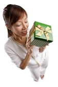 Woman standing, holding gift - Asia Images Group
