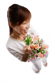 Woman standing, holding bouquet of flowers, looking away - Asia Images Group