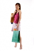 Woman standing, carrying shopping bags, looking away - Asia Images Group