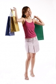 Woman standing, carrying shopping bags in both hands, looking away - Asia Images Group