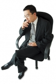 Businessman sitting on office chair, hand on chin - Asia Images Group