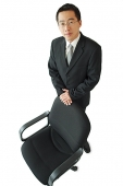 Businessman standing next to office chair, looking at camera - Asia Images Group