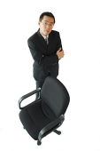 Businessman standing next to office chair, arms crossed - Asia Images Group