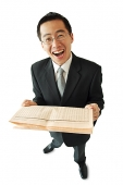 Businessman holding newspaper, laughing - Asia Images Group
