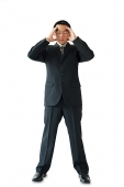 Businessman standing with hands on head - Asia Images Group