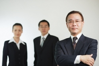 Businessman with arms crossed, looking at camera, two executives behind him - Asia Images Group