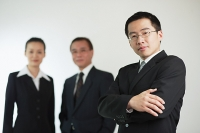 Young businessman with arms crossed, businessman and businesswoman in the background - Asia Images Group