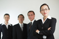 Businesswoman with arms crossed, other executives in the background - Asia Images Group