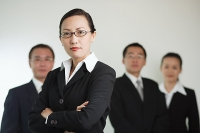 Group of businesspeople, businesswoman in the foreground with arms crossed - Asia Images Group