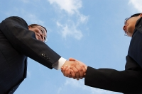 Two businessmen shaking hands, low angle view - Asia Images Group