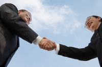 Businessman and businesswoman shaking hands, low angle view - Asia Images Group