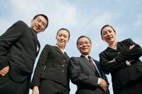 Businessmen and businesswomen looking down at camera - Asia Images Group