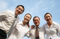 Executives looking down at camera, arms around each other, smiling - Asia Images Group