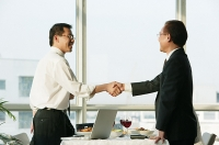 Businessmen shaking hands over lunch table - Asia Images Group