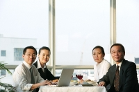 Executives sitting at lunch table, looking at camera - Asia Images Group