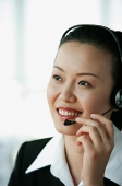 Woman wearing headset, smiling, portrait - Asia Images Group