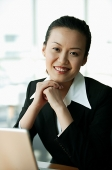 Businesswoman smiling at camera, hands clasped - Asia Images Group
