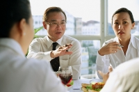 Executives having lunch meeting, over the shoulder view - Asia Images Group