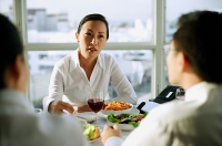 Businesswoman facing other executives over lunch table - Asia Images Group