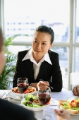 Businesswoman sitting at lunch table, over the shoulder view - Asia Images Group